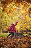 Happy child girl playing with autumn leaves on the walk in sunny autumn day. Happy child girl in red coat playing with autumn leaves on the walk in sunny autumn Stock Photo