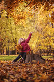 Happy child girl playing with autumn leaves on the walk in sunny autumn day Stock Image