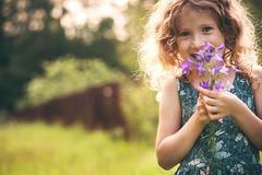 Happy child girl playing with bouquet of bluebells in summer. Royalty Free Stock Image