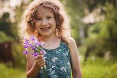 Happy child girl playing with bouquet of bluebells in summer. Royalty Free Stock Photos