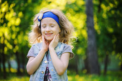 Happy child girl playing on colorful spring field. Blooming dandelions on background, outdoor seasonal activities. Cozy warm mood Stock Photo