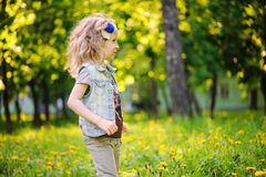 Happy child girl playing on colorful spring field. Blooming dandelions on background, outdoor seasonal activities. Stock Photos