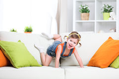 Happy child girl playing on couch at home. Happy funny child girl playing  on the couch at home Royalty Free Stock Photography