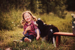 Happy child girl playing with her dog in summer day Stock Photography