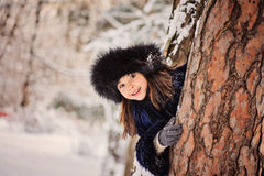 Happy child girl playing hide and seek in winter forest. Happy child girl in fur hat and coat playing hide and seek in winter forest Royalty Free Stock Photography