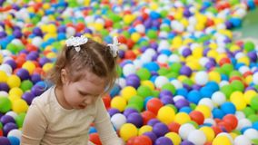 Happy child girl playing and hiding on the playground with multicolored balloons. Happy child girl playing and hiding on the playground with multicolored stock video footage