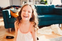 Happy child girl having fun at home in lazy weekend morning. Happy child girl playing at home in cozy weekend morning, having fun on couch in modern living room Royalty Free Stock Images