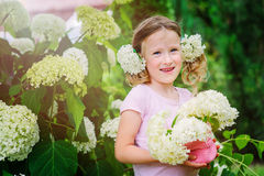 Happy child girl playing with hydrangea bouquet in summer garden Stock Images