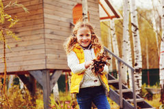 Happy child girl playing little gardener in autumn and picking leaves into basket Royalty Free Stock Photos