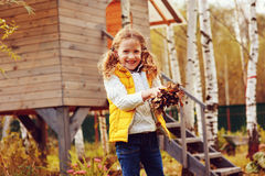 Happy child girl playing little gardener in autumn and picking leaves into basket. Seasonal garden work. Stock Images
