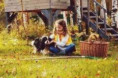 Happy child girl playing little gardener in autumn and picking leaves into basket. Seasonal garden work. Stock Photography