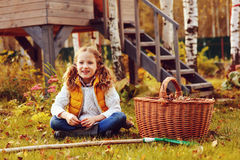 Happy child girl playing little gardener in autumn and picking leaves into basket. Seasonal garden work. Stock Photo