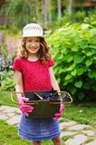 Happy child girl playing little gardener and helping in summer garden. Wearing hat and gloves, working with tools. Vertical capture Stock Photography