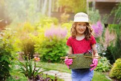 Happy child girl playing little gardener and helping in summer garden, wearing hat and gloves. Working with tools. Vertical capture Royalty Free Stock Photos