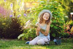 happy child girl playing little gardener in summer, wearing funny hat and holding bouquet of flowers Stock Photos