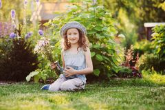 Happy child girl playing little gardener in summer, wearing funny hat and holding bouquet of flowers. Sitting on green lawn, enjoying summertime vacations Stock Photography