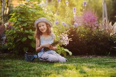 Happy child girl playing little gardener in summer, wearing funny hat and holding bouquet of flowers. Sitting on green lawn, enjoying summertime vacations Stock Image