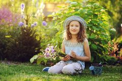 Happy child girl playing little gardener in summer, wearing funny hat and holding bouquet of flowers stock photography