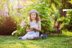 happy child girl playing little gardener in summer, wearing funny hat and holding bouquet of flowers Royalty Free Stock Image