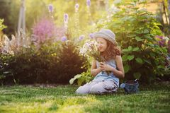 Happy child girl playing little gardener in summer, wearing funny hat and holding bouquet of flowers. Sitting on green lawn, enjoying summertime vacations Royalty Free Stock Images
