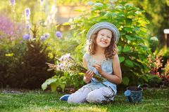 Happy child girl playing little gardener in summer, wearing funny hat and holding bouquet of flowers. Sitting on green lawn, enjoying summertime vacations Royalty Free Stock Photo