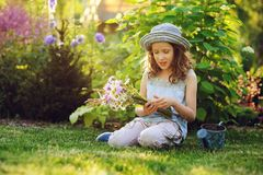 Happy child girl playing little gardener in summer, wearing funny hat and holding bouquet of flowers Royalty Free Stock Photography
