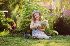 happy child girl playing little gardener in summer, wearing funny hat and holding bouquet of flowers. royalty free stock photos