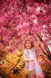 Happy child girl playing outdoor with blooming crabapple tree in spring Stock Image