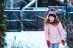 Happy child girl playing outdoor in snowy winter garden stock image