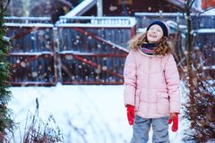 happy child girl playing outdoor in snowy winter garden royalty free stock images