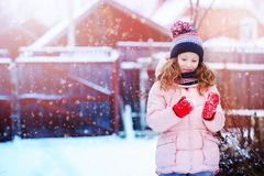 Happy child girl playing outdoor in snowy winter garden. stock photography