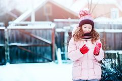 Happy child girl playing outdoor in snowy winter garden royalty free stock photo