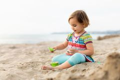 Happy Girl Playing with Sand at Beach in a Summer Evening stock photography