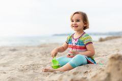 Happy Girl Playing with Sand at Beach in a Summer Evening royalty free stock image