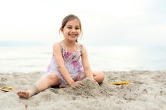 Happy Girl Playing with Sand at Beach in a Summer Evening royalty free stock photo