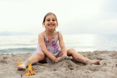 Happy Girl Playing with Sand at Beach in a Summer Evening stock images