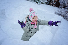 Happy child girl playing in snow castle in dropping snowballs Stock Photos