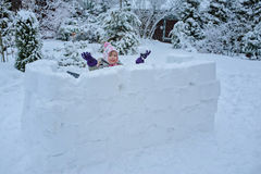Happy child girl playing in snow castle in dropping snowballs on winter backyard Stock Images