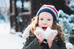 Happy child girl playing with snow on snowy winter walk on backyard Stock Images