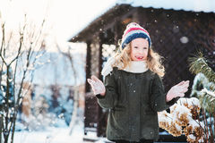 Happy child girl playing with snow on snowy winter walk on backyard Royalty Free Stock Image