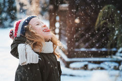 Happy child girl playing with snow on snowy winter walk on backyard Royalty Free Stock Photos