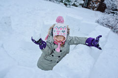 Happy child girl playing snowballs in snow castle on backyard Stock Images