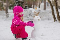 Happy child girl playing with a snowman Royalty Free Stock Photos