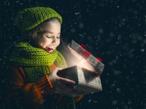 Kid with gift box on dark background. Happy child girl playing on a snowy winter walk. Little girl enjoys the game. Child girl playing outdoors in snow. Outdoor royalty free stock photos
