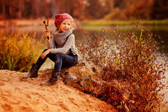 Happy child girl playing with stick on sunny autumn riverside Royalty Free Stock Images