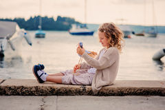 Happy child girl playing with toy bird on summer seacoast Royalty Free Stock Image
