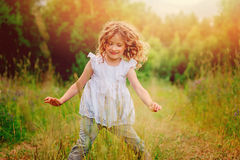 Happy child girl playing on the walk on summer field Stock Photos