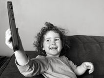 Happy child girl plays on mobile phone Stock Image