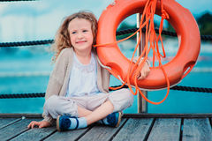 Happy child girl plays with rescue ring on wooden pier with sea background Royalty Free Stock Photos