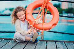 Happy child girl plays with rescue ring on wooden pier with sea background Stock Image
